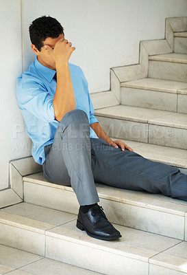 Buy stock photo Male executive sitting on steps with hand on forehead