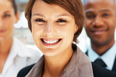 Buy stock photo Closeup view of pretty executive smiling with colleagues in background