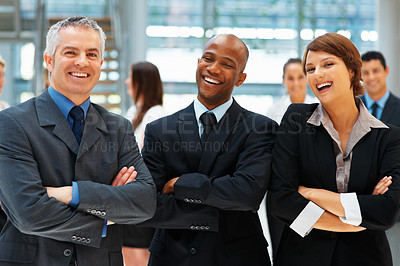Buy stock photo Group of executives smiling while standing with arms folded