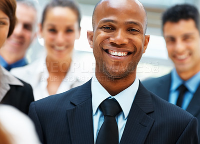 Buy stock photo Closeup of smiling businessman with team in background
