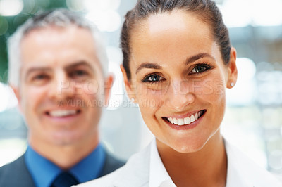 Buy stock photo Focus on woman smiling with colleague behind her