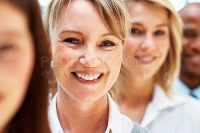 Buy stock photo Focus on female executive with colleagues in front and back of her