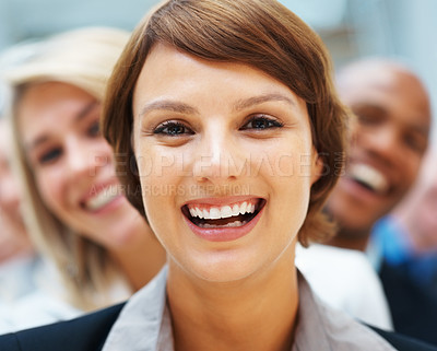 Buy stock photo Closeup of pretty executive with team smiling behind her