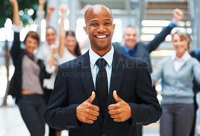 Buy stock photo Businessman giving two thumbs up with enthusiastic colleagues in background