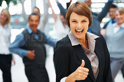 Buy stock photo Focus on enthusiastic businesswoman with thumbs up and excited colleagues in background