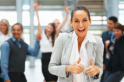 Buy stock photo Female executive giving thumbs up with excited team behind her