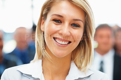 Buy stock photo Closeup of friendly businesswoman with team in distance
