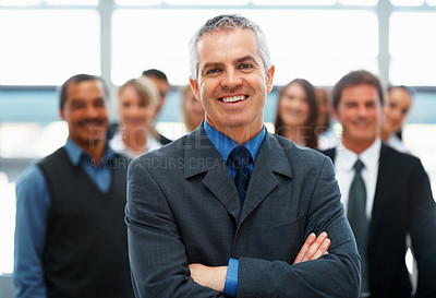 Buy stock photo Senior executive standing with hands folded in front of team