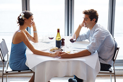 Buy stock photo Happy and romantic young couple on a date at the restaurant