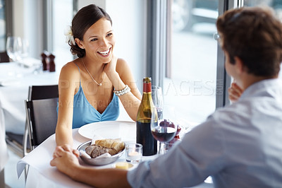 Buy stock photo An attractive young woman on a romantic date in a brightly lit stylish restaurant