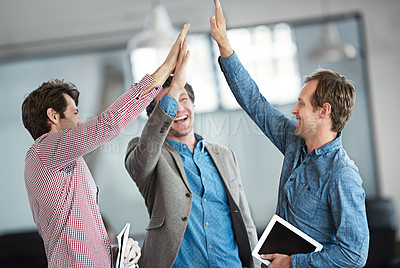 Buy stock photo Shot of a group of male coworkers high-fiving in an office
