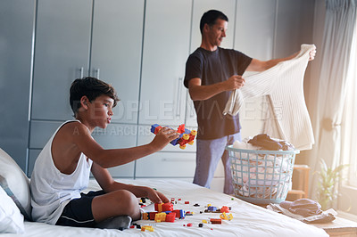 Buy stock photo Cropped shot of a young boy playing with toys while his father folds laundry in the background