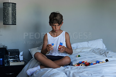 Buy stock photo Shot of a young boy playing with toys on his bed at home