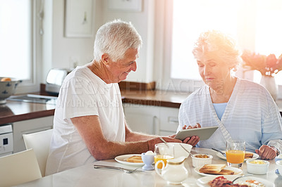 Buy stock photo Cropped shot of a senior couple using a digital tablet while having breakfast at home
