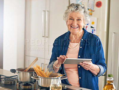 Buy stock photo Portrait of a senior woman using a digital tablet while cooking in her kitchen