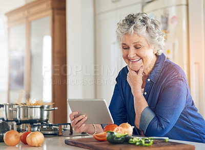 Buy stock photo Cropped shot of a senior woman using a digital tablet while cooking in her kitchen