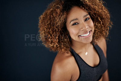 Buy stock photo Portrait of a happy woman in sportswear posing against a dark background