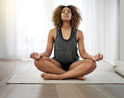 Buy stock photo Shot of a serene young woman doing yoga by herself at home