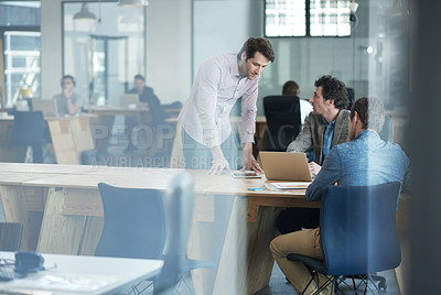 Buy stock photo Shot of a group of colleagues talking together over a laptop in an office