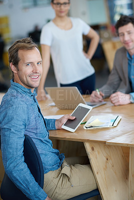 Buy stock photo Portrait of a designer sitting at a table holding a digital tablet with colleagues in the background
