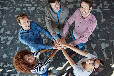 Buy stock photo High angle portrait of a group of smiling coworkers standing in hand in hand in a huddle in an office