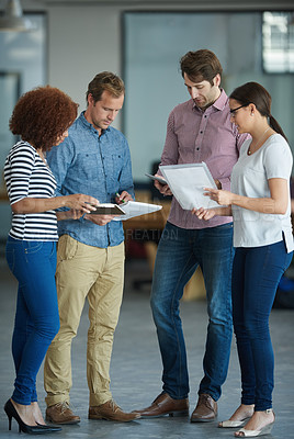 Buy stock photo Shot of a group of colleagues discussing paperwork while standing in an office
