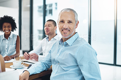 Buy stock photo Portrait of a mature businessman sitting in a meeting with his colleagues in the background
