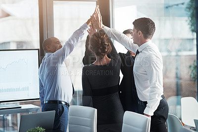 Buy stock photo Shot of a group of businesspeople high fiving together while standing in a modern boardroom