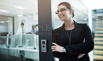 Buy stock photo Shot of a young businesswoman standing with her arms crossed in an office doorway
