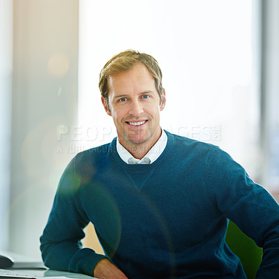 Buy stock photo Portrait of a smiling businessman sitting at a desk in a modern office