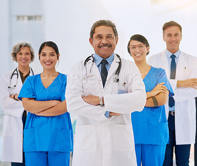 Buy stock photo Portrait of a medical team standing with their arms folded in a hospital