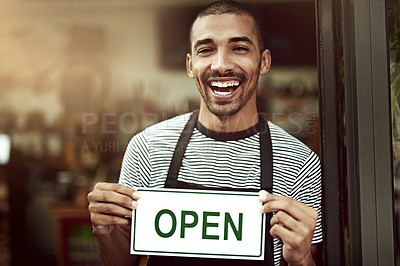 Buy stock photo Portrait of a young man holding up an open sign in his store