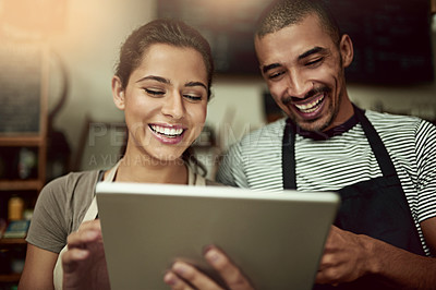 Buy stock photo Shot of a young man and woman using a digital tablet together while working in a coffee shop
