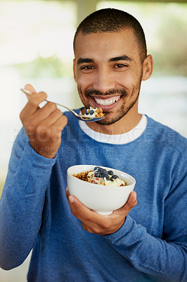 Buy stock photo Portrait of a happy young man enjoying a bowl of muesli at home