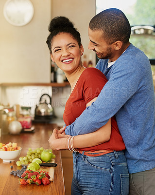 Buy stock photo Shot of a young man hugging his wife while she prepares a healthy snack at home