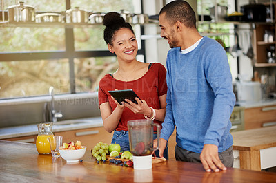 Buy stock photo Shot of a happy young couple using a digital tablet while preparing a healthy snack together at home