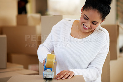 Buy stock photo Shot of a happy young woman packing boxes while moving house