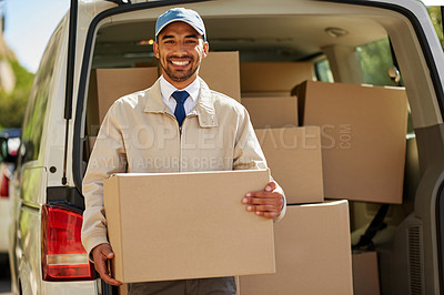Buy stock photo Portrait of a friendly delivery man unloading cardboard boxes from his van