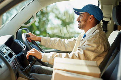 Buy stock photo Shot of a happy delivery man driving his van with boxes in the front seat