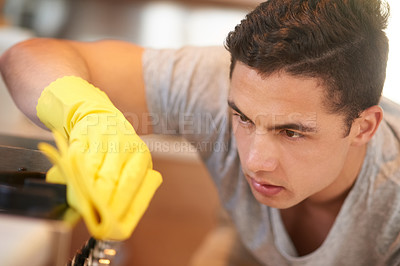 Buy stock photo Shot of a focused young man cleaning his kitchen