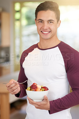 Buy stock photo Portrait of a happy young man enjoying a healthy breakfast of fruit in his kitchen at home
