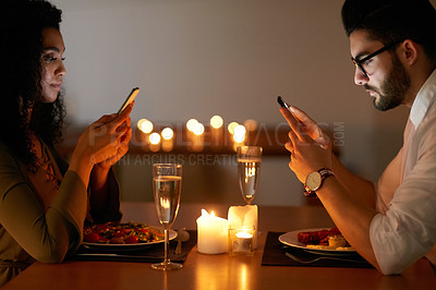 Buy stock photo Shot of a young couple texting on their phones while out for dinner