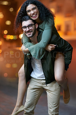 Buy stock photo Portrait of a handsome young man piggybacking his girlfriend outdoors at night