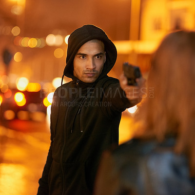 Buy stock photo Shot of a thief threatening a young woman at gunpoint in the city