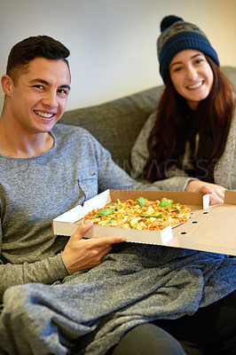 Buy stock photo Portrait of a happy young couple eating pizza while relaxing on the sofa at home
