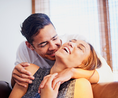 Buy stock photo Shot of a laughing young couple sharing a moment together at home