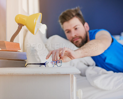 Buy stock photo Cropped shot of a young man reaching for his spectacles after waking up from bed