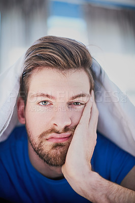Buy stock photo Portrait of a handsome young man looking bored while lying in bed