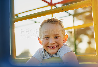 Buy stock photo Portrait of a smiling little boy playing on a jungle gym in the park