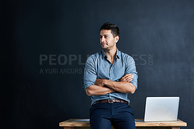 Buy stock photo Cropped shot of a handsome young businessman standing in front of a desk against a dark background